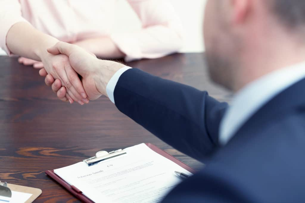 Man shaking hands with woman after a successful job interview